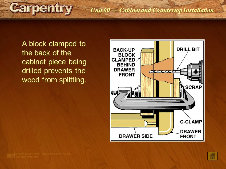 A block clamped to the back of the cabinet piece being drilled prevents the wood from splitting.