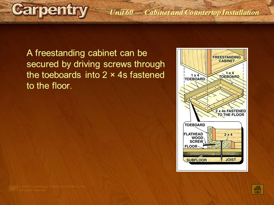 A freestanding cabinet can be secured by driving screws through the toeboards into 2 × 4s fastened to the floor.