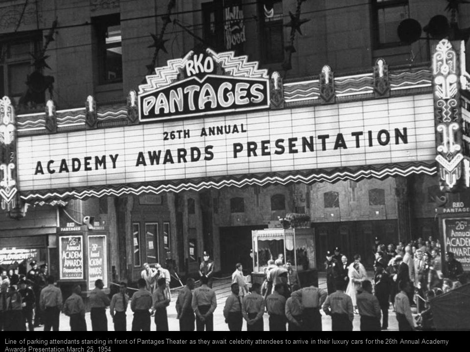 Line of parking attendants standing in front of Pantages Theater as they await celebrity attendees to arrive in their luxury cars for the 26th Annual Academy Awards Presentation.March 25, 1954