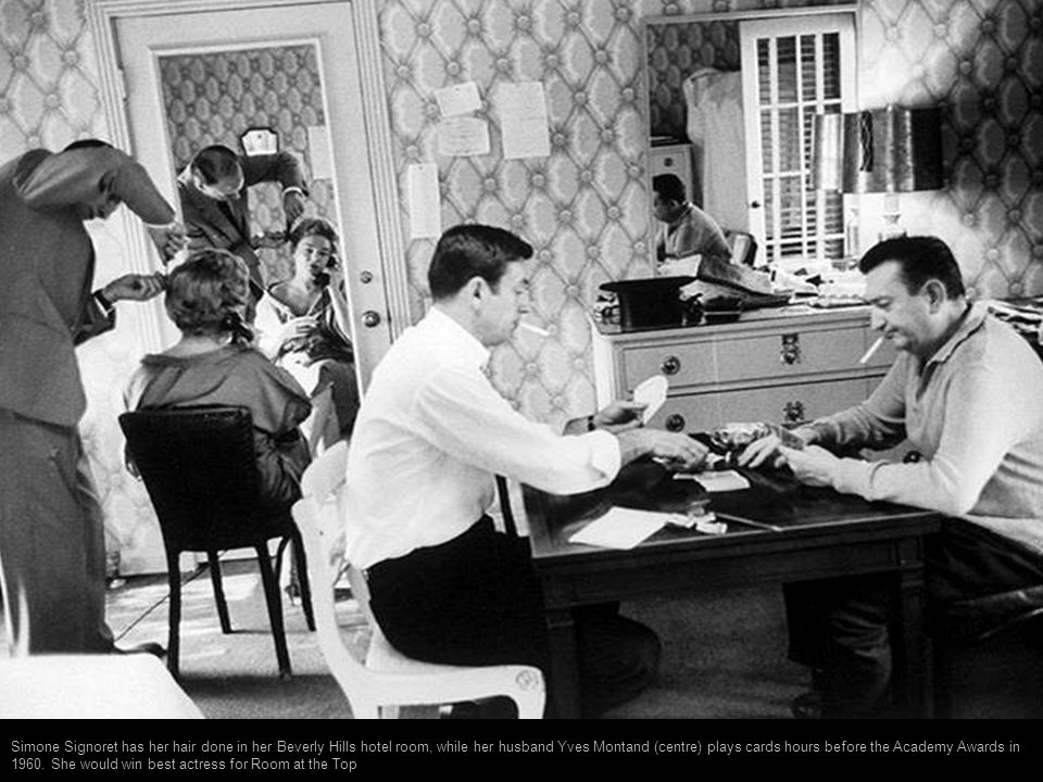 Simone Signoret has her hair done in her Beverly Hills hotel room, while her husband Yves Montand (centre) plays cards hours before the Academy Awards in 1960.