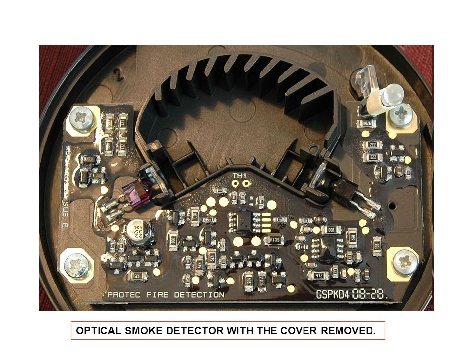 OPTICAL SMOKE DETECTOR WITH THE COVER REMOVED.