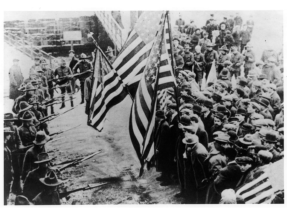fig18_20.jpg Page 696: Striking textile workers at Lawrence, Massachusetts in 1912, carrying American flags, were confronted by the state militia.