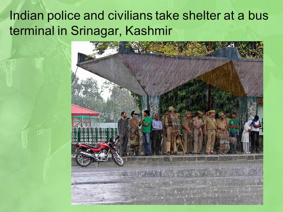 Indian police and civilians take shelter at a bus terminal in Srinagar, Kashmir