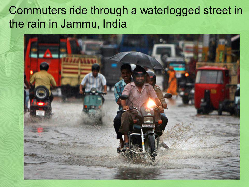 Commuters ride through a waterlogged street in the rain in Jammu, India
