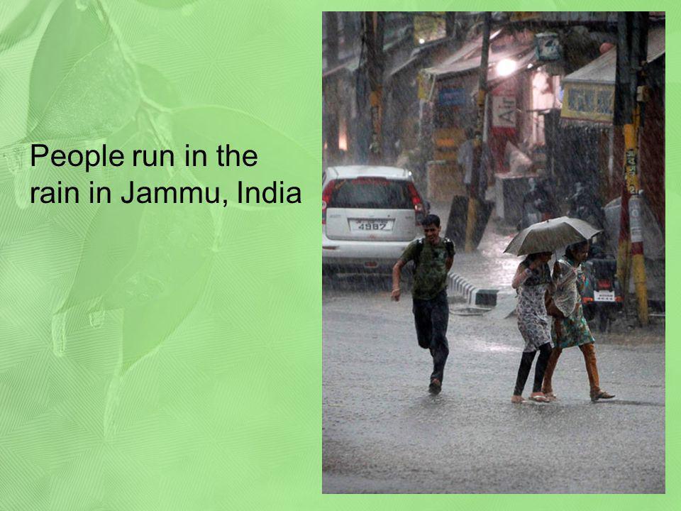People run in the rain in Jammu, India