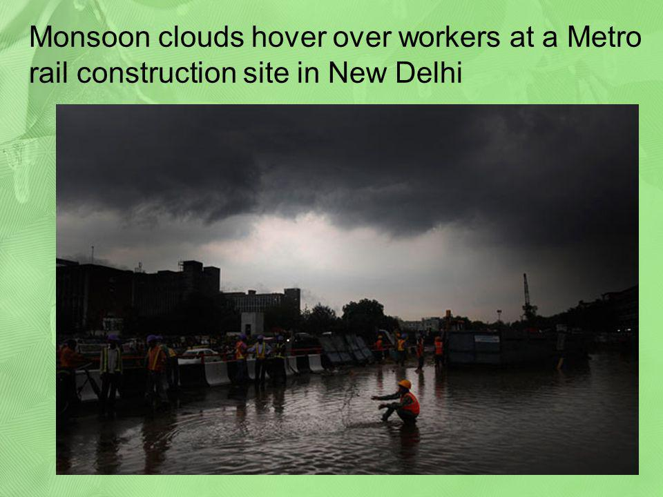 Monsoon clouds hover over workers at a Metro rail construction site in New Delhi