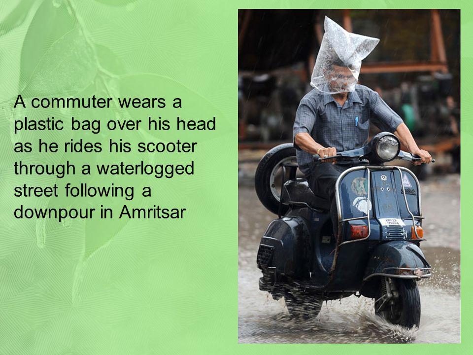 A commuter wears a plastic bag over his head as he rides his scooter through a waterlogged street following a downpour in Amritsar