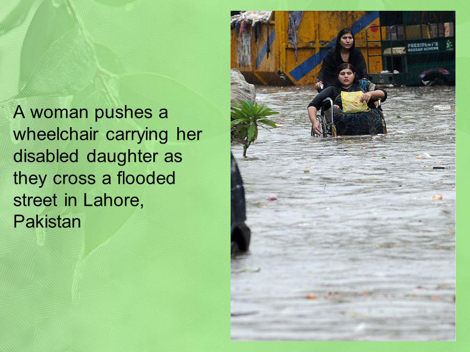 A woman pushes a wheelchair carrying her disabled daughter as they cross a flooded street in Lahore, Pakistan