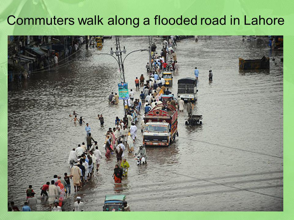 Commuters walk along a flooded road in Lahore