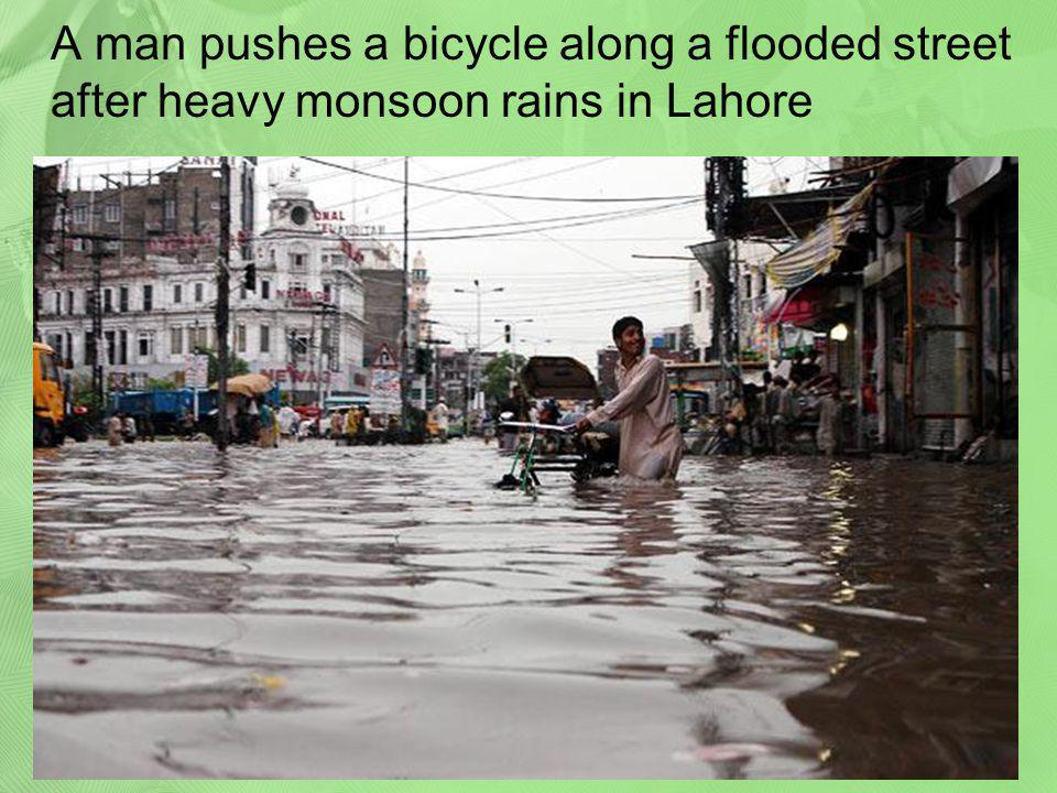 A man pushes a bicycle along a flooded street after heavy monsoon rains in Lahore