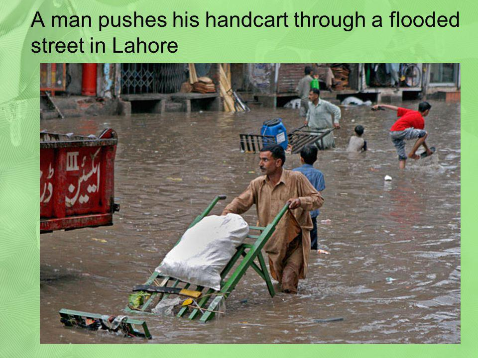 A man pushes his handcart through a flooded street in Lahore