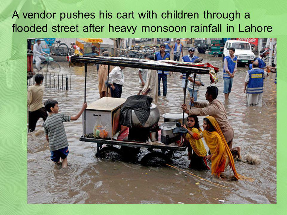 A vendor pushes his cart with children through a flooded street after heavy monsoon rainfall in Lahore