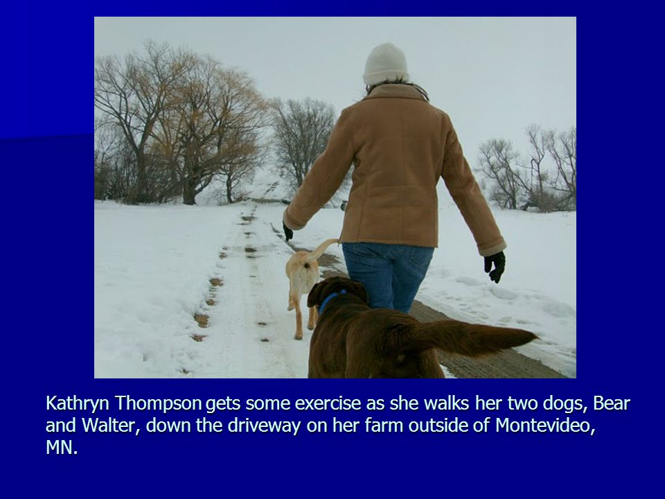 Kathryn Thompson gets some exercise as she walks her two dogs, Bear and Walter, down the driveway on her farm outside of Montevideo, MN.