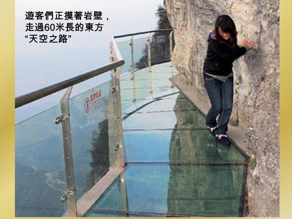 遊客們正摸著岩壁, 走過60米長的東方 天空之路