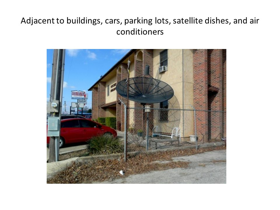 Adjacent to buildings, cars, parking lots, satellite dishes, and air conditioners