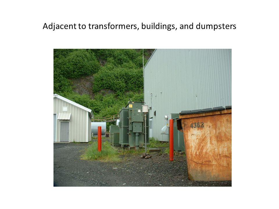 Adjacent to transformers, buildings, and dumpsters