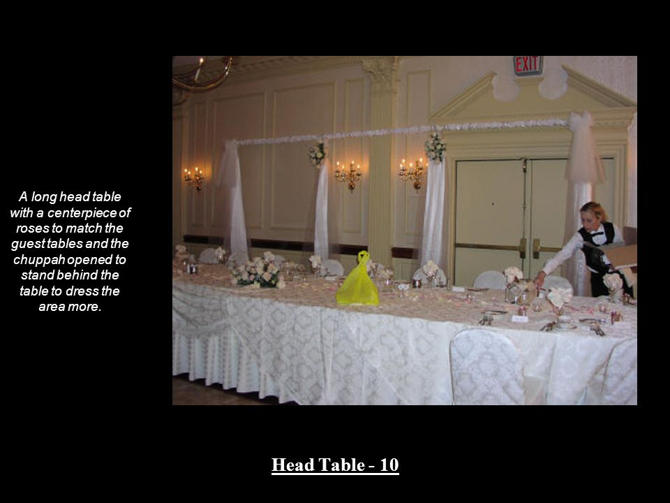 A long head table with a centerpiece of roses to match the guest tables and the chuppah opened to stand behind the table to dress the area more.