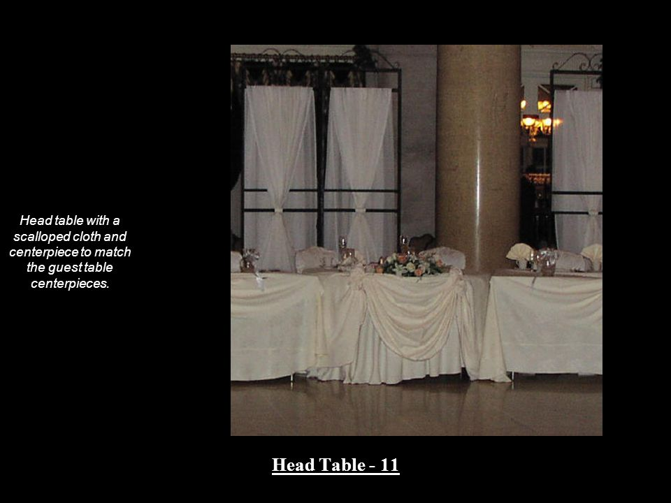 Head table with a scalloped cloth and centerpiece to match the guest table centerpieces.