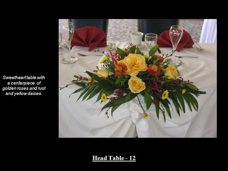 Sweetheart table with a centerpiece of golden roses and rust and yellow daises.