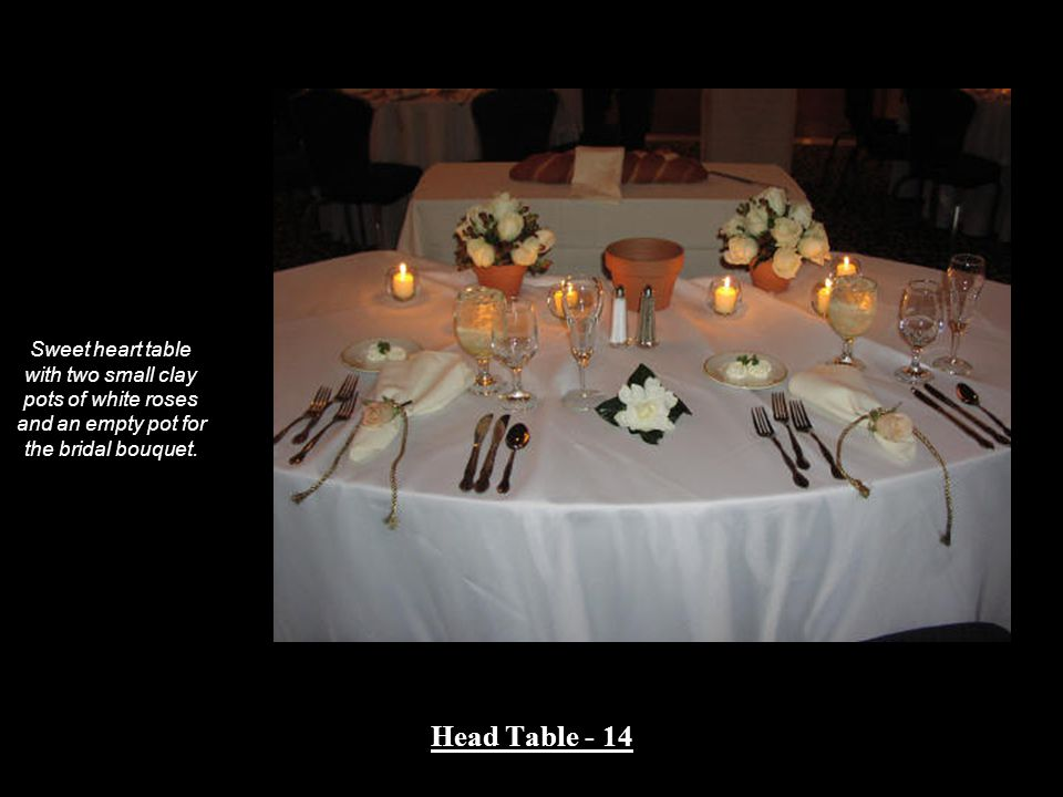 Sweet heart table with two small clay pots of white roses and an empty pot for the bridal bouquet.