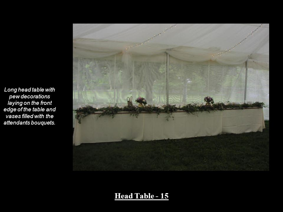 Long head table with pew decorations laying on the front edge of the table and vases filled with the attendants bouquets.