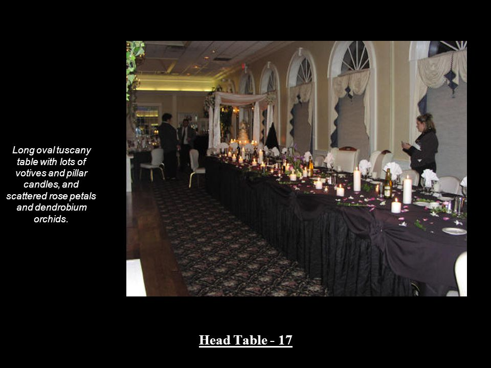 Long oval tuscany table with lots of votives and pillar candles, and scattered rose petals and dendrobium orchids.