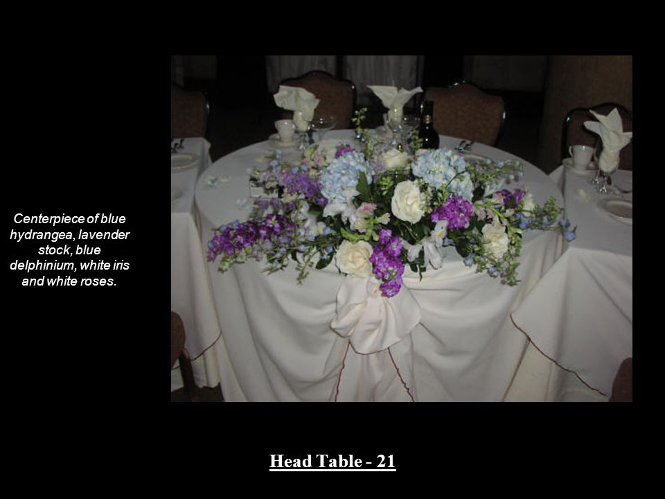 Centerpiece of blue hydrangea, lavender stock, blue delphinium, white iris and white roses.