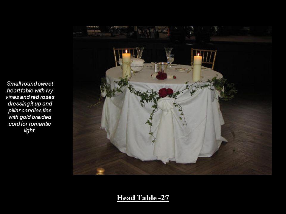 Small round sweet heart table with ivy vines and red roses dressing it up and pillar candles ties with gold braided cord for romantic light.