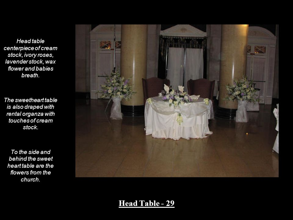 Head table centerpiece of cream stock, ivory roses, lavender stock, wax flower and babies breath.