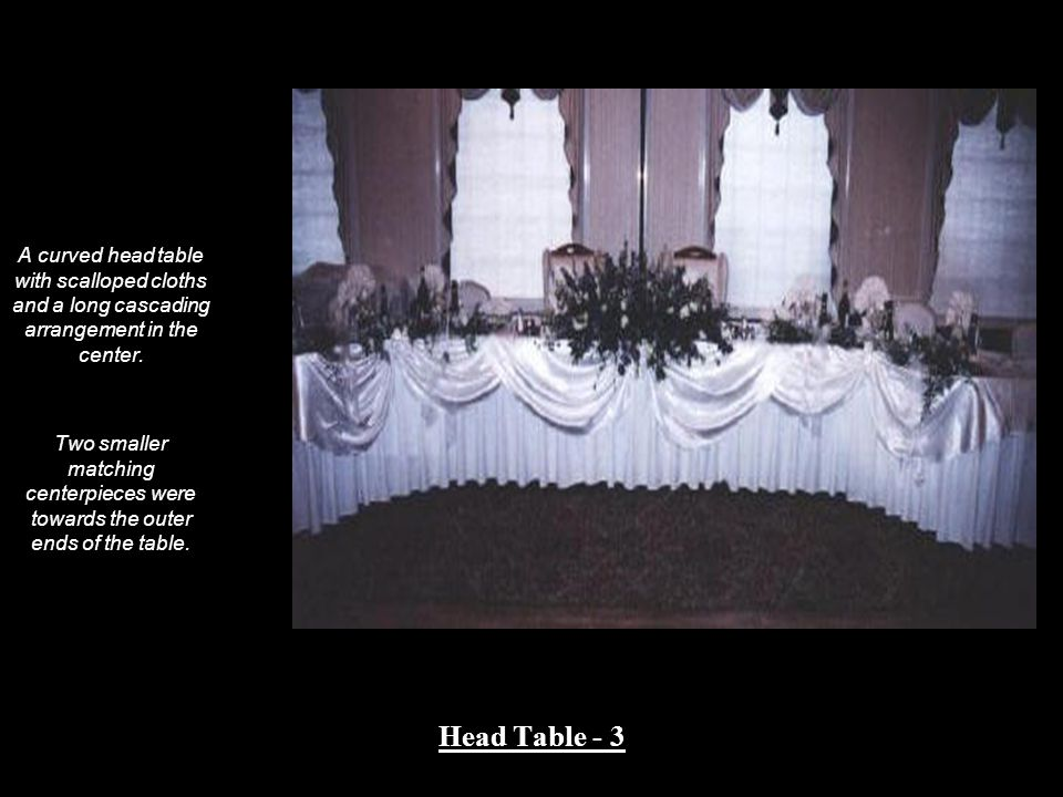 A curved head table with scalloped cloths and a long cascading arrangement in the center.
