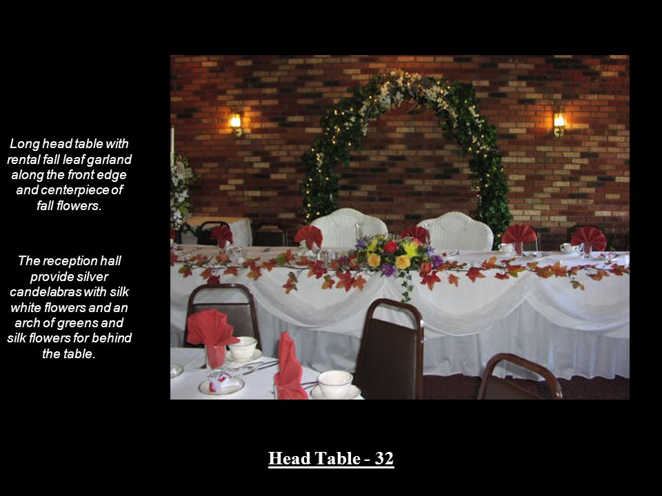 Long head table with rental fall leaf garland along the front edge and centerpiece of fall flowers.