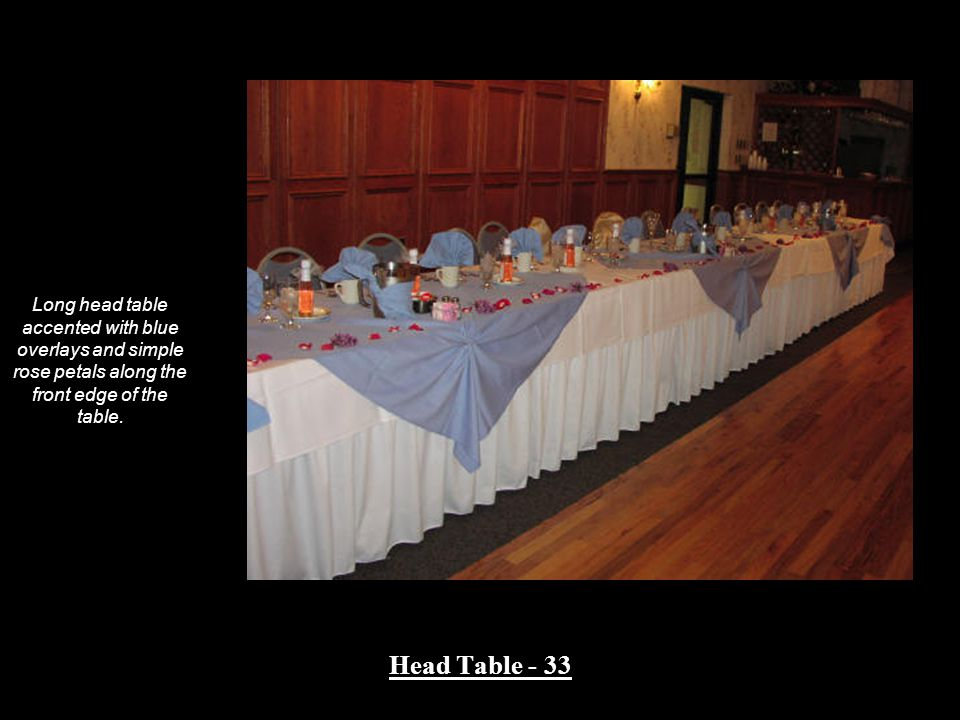 Long head table accented with blue overlays and simple rose petals along the front edge of the table.