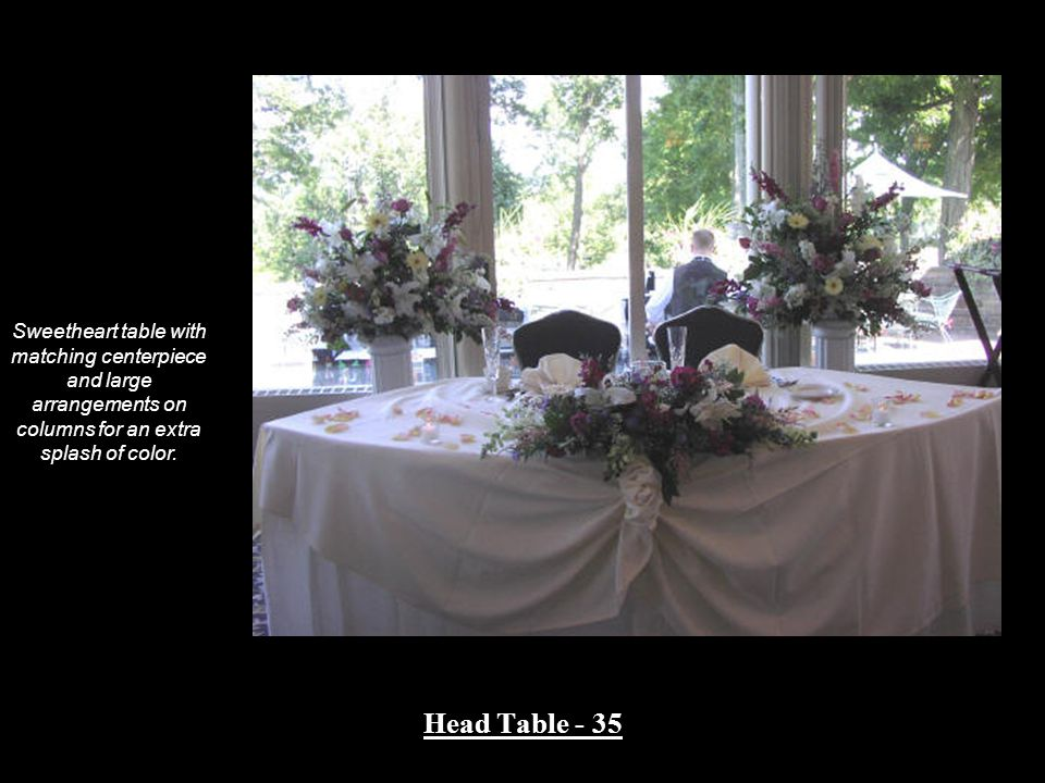 Sweetheart table with matching centerpiece and large arrangements on columns for an extra splash of color.