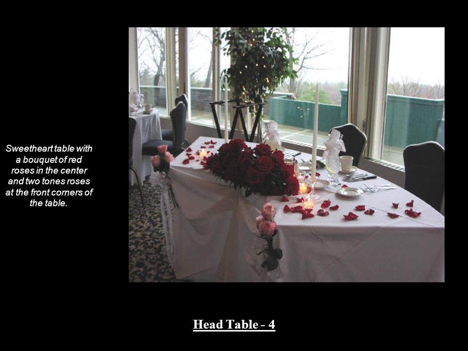 Sweetheart table with a bouquet of red roses in the center and two tones roses at the front corners of the table.