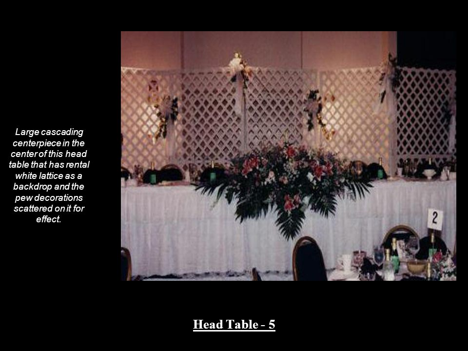 Large cascading centerpiece in the center of this head table that has rental white lattice as a backdrop and the pew decorations scattered on it for effect.