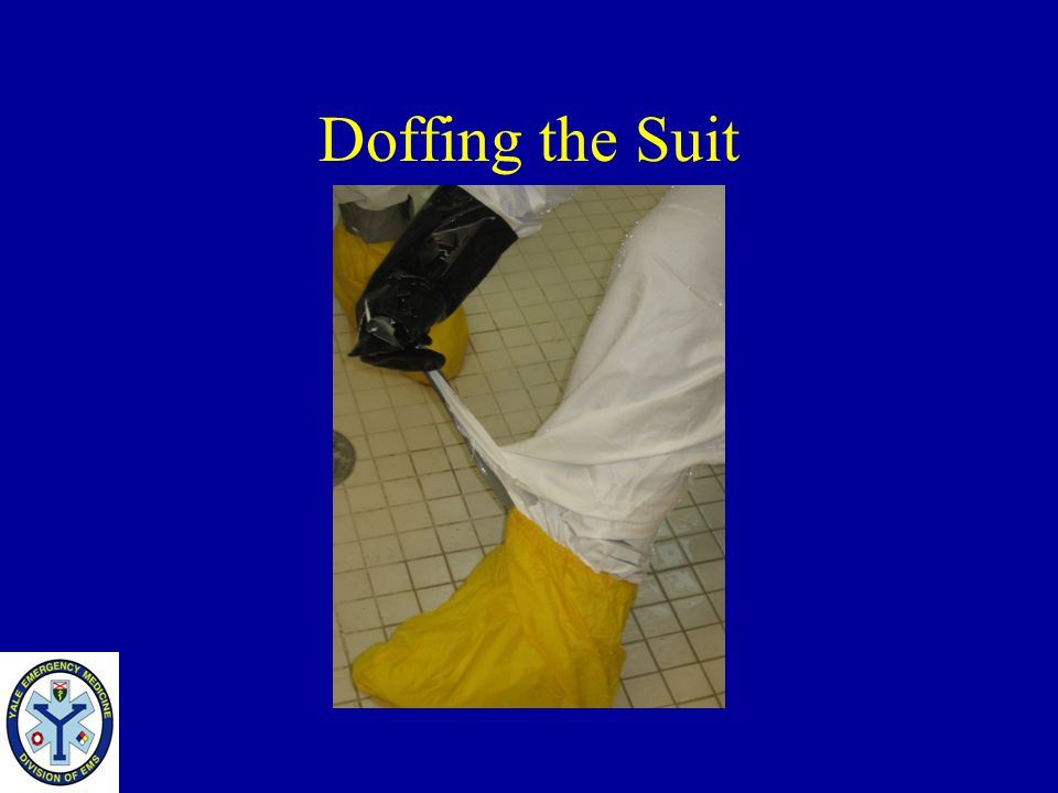Doffing the Suit Once the tape covering the front zipper is removed, remove the tape from the outer boots.