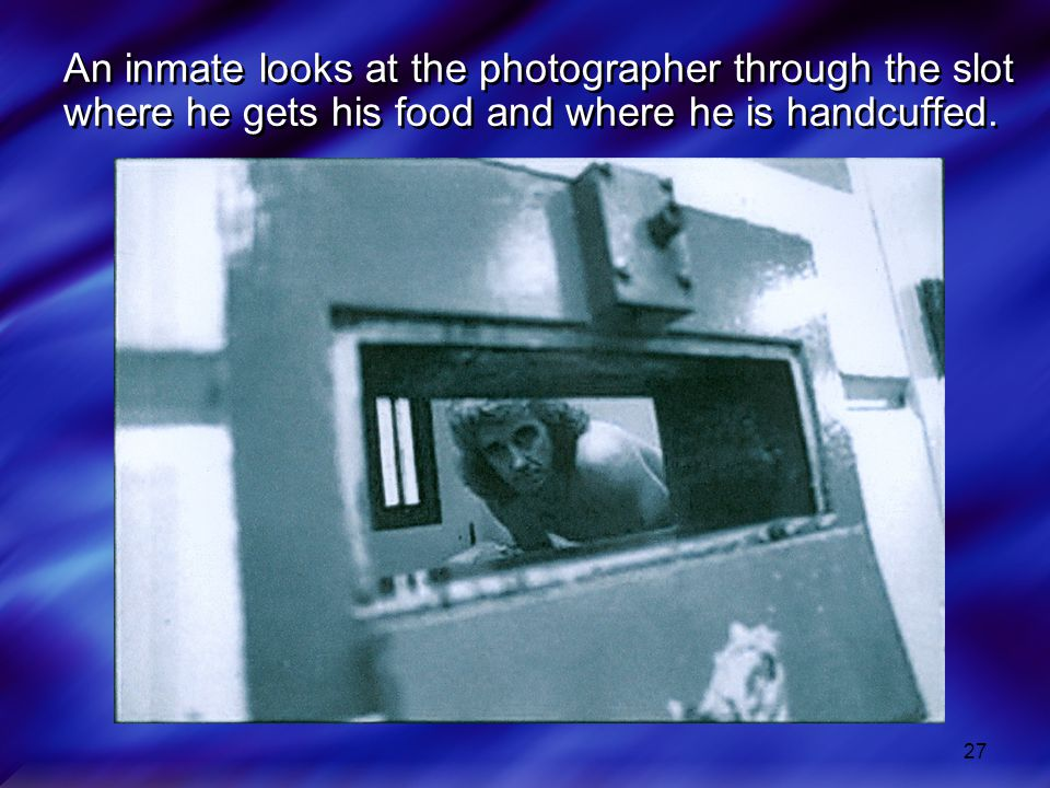 An inmate looks at the photographer through the slot where he gets his food and where he is handcuffed.