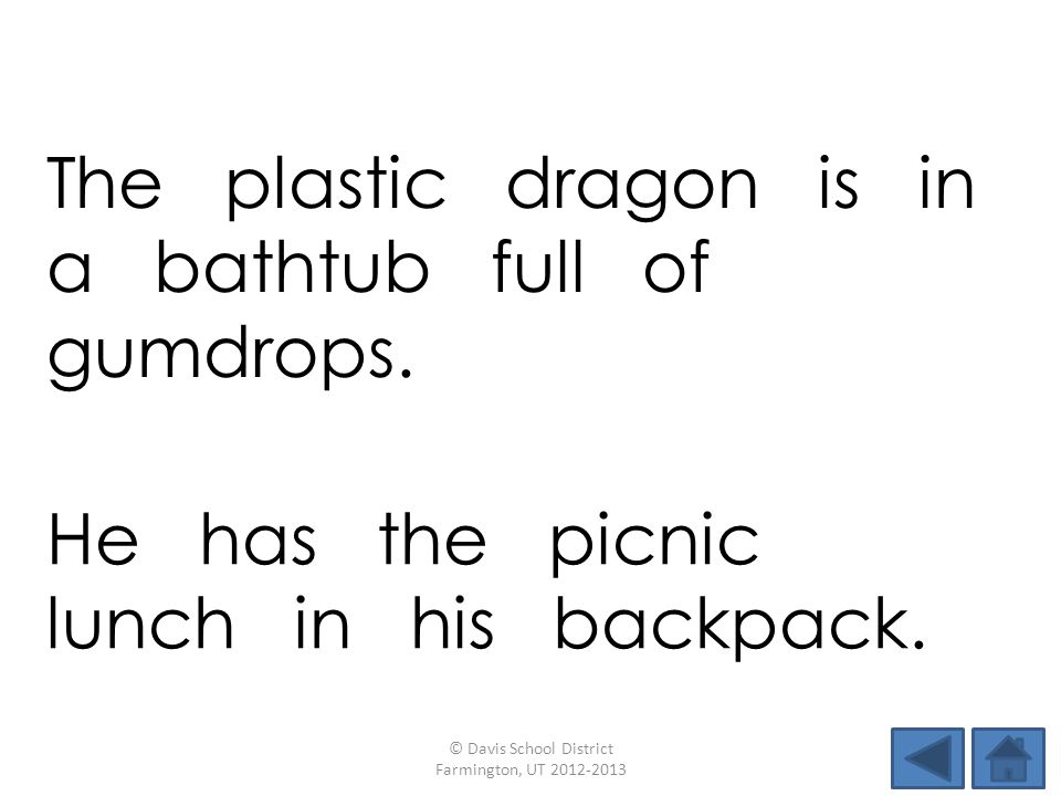 The plastic dragon is in a bathtub full of gumdrops.