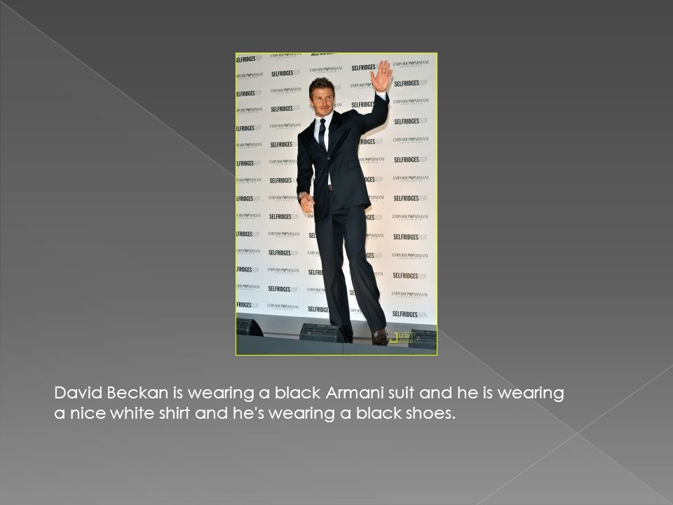 David Beckan is wearing a black Armani suit and he is wearing a nice white shirt and he s wearing a black shoes.