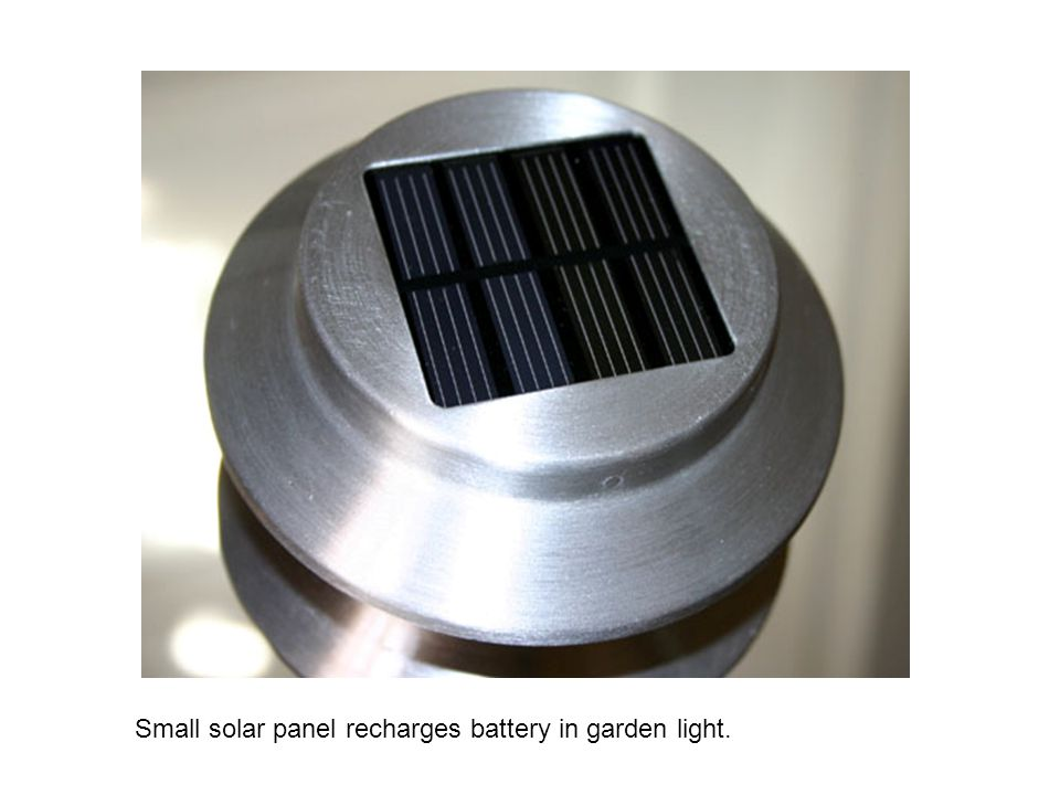 Small solar panel recharges battery in garden light.