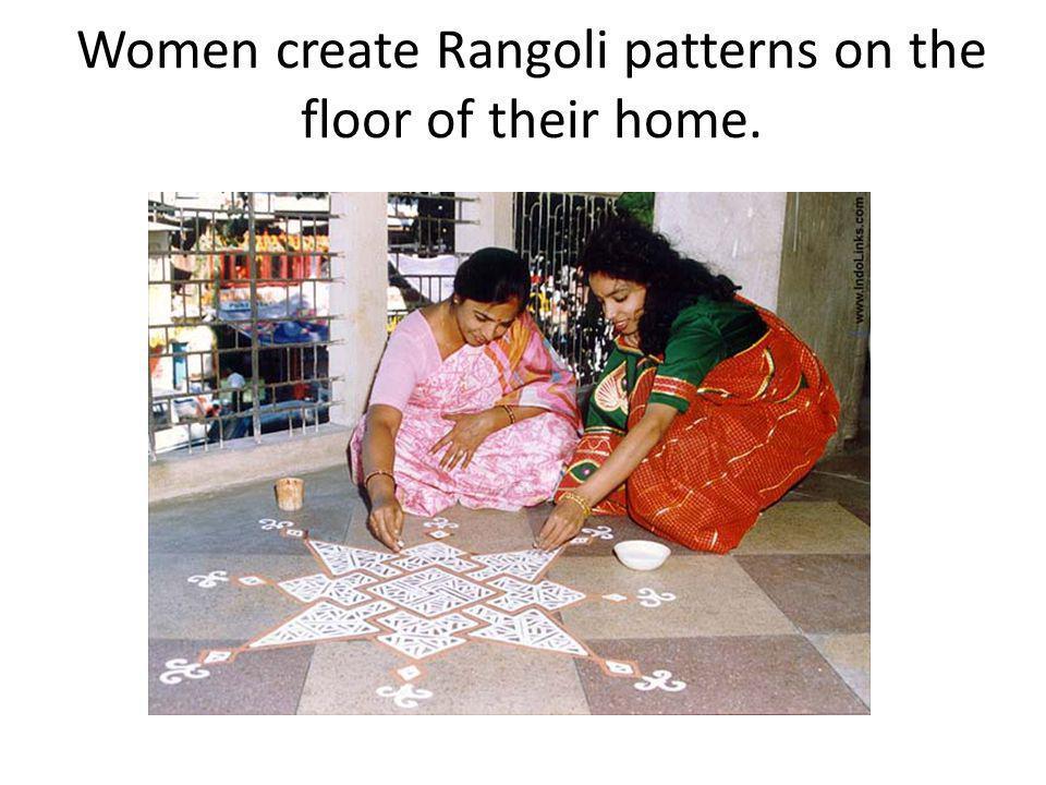Women create Rangoli patterns on the floor of their home.