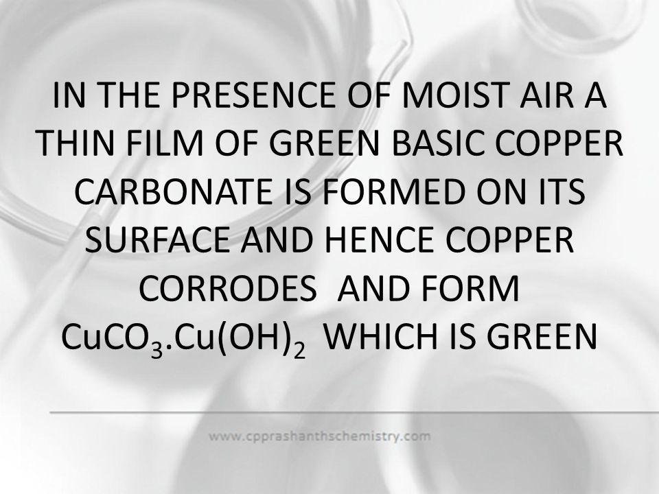 IN THE PRESENCE OF MOIST AIR A THIN FILM OF GREEN BASIC COPPER CARBONATE IS FORMED ON ITS SURFACE AND HENCE COPPER CORRODES AND FORM CuCO3.Cu(OH)2 WHICH IS GREEN