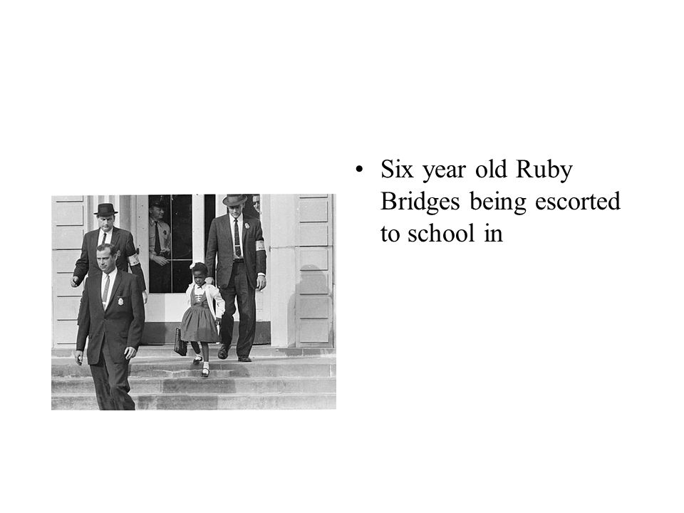 Six year old Ruby Bridges being escorted to school in