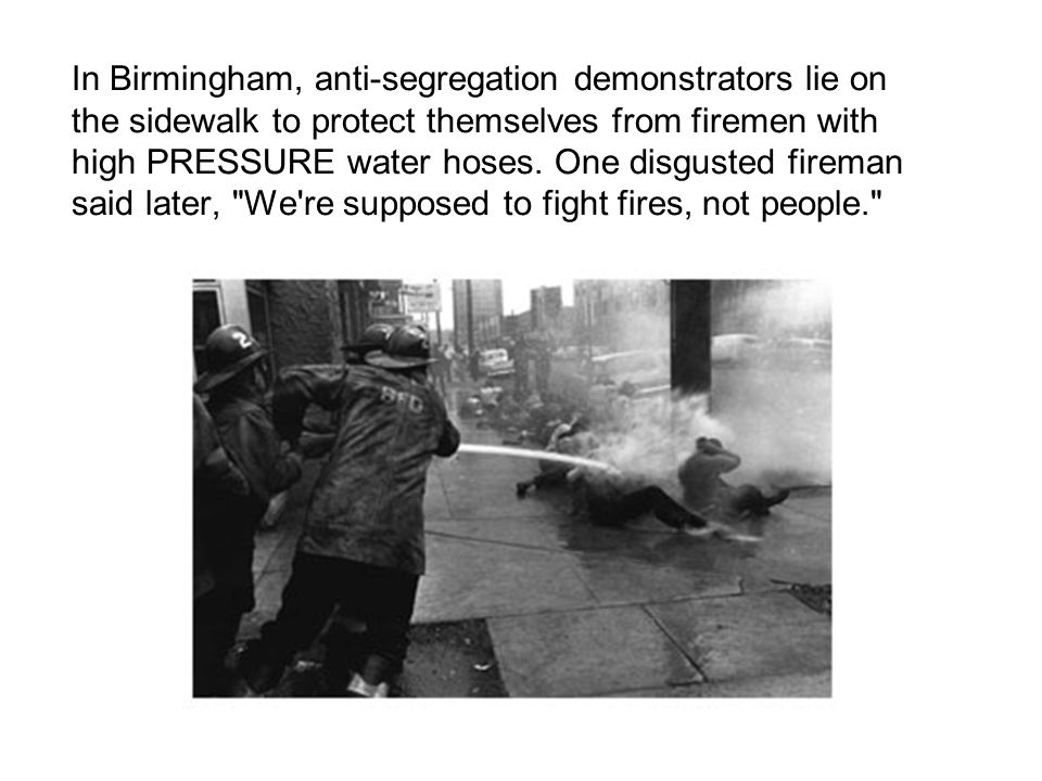 In Birmingham, anti-segregation demonstrators lie on the sidewalk to protect themselves from firemen with high PRESSURE water hoses.