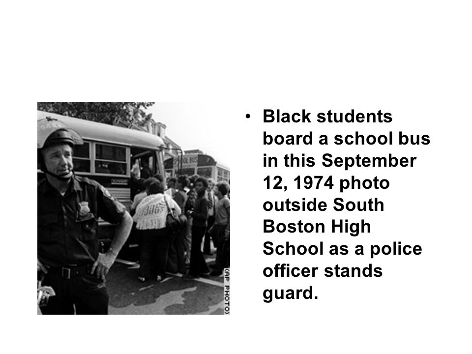 Black students board a school bus in this September 12, 1974 photo outside South Boston High School as a police officer stands guard.