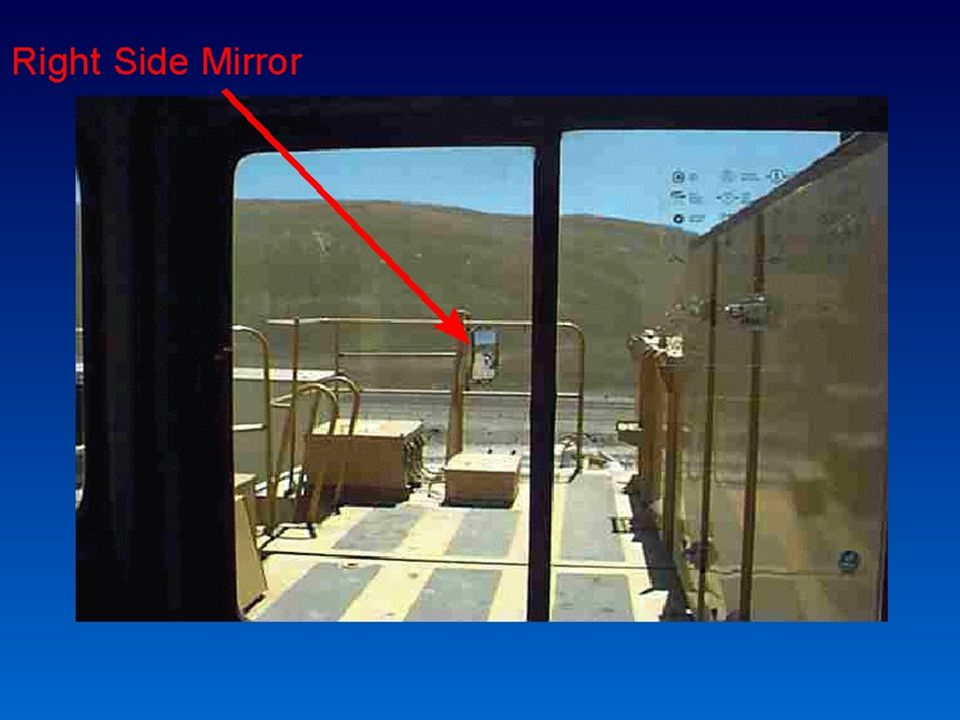 In this view from the driver's seat you can see the convex mirror on the right side. This mirror can be as much as 20 to 25 feet away from the driver on larger trucks. You can see that the image is not very big, and it's often blurred. Sometimes the mirror is reflecting the same shade of color as the background view. It's very hard for the driver to see that far away. Painting a bright colored border around that mirror could help the driver pick it out quicker.