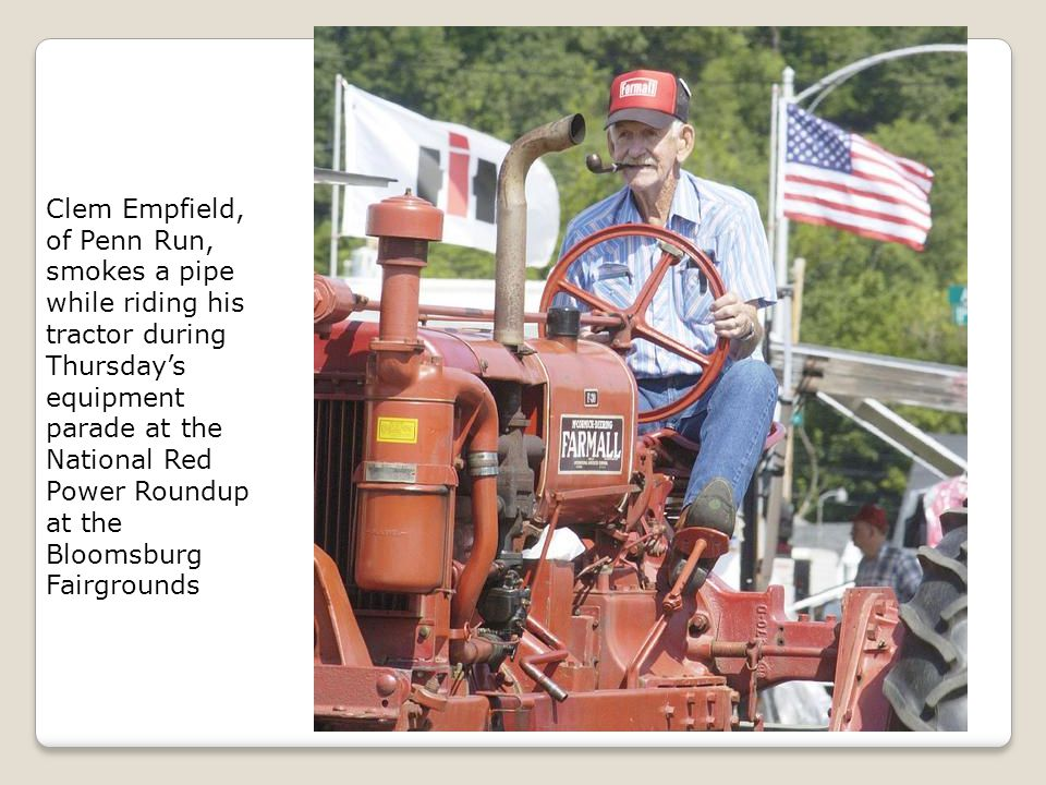 Clem Empfield, of Penn Run, smokes a pipe while riding his tractor during Thursday's equipment parade at the National Red Power Roundup at the Bloomsburg Fairgrounds