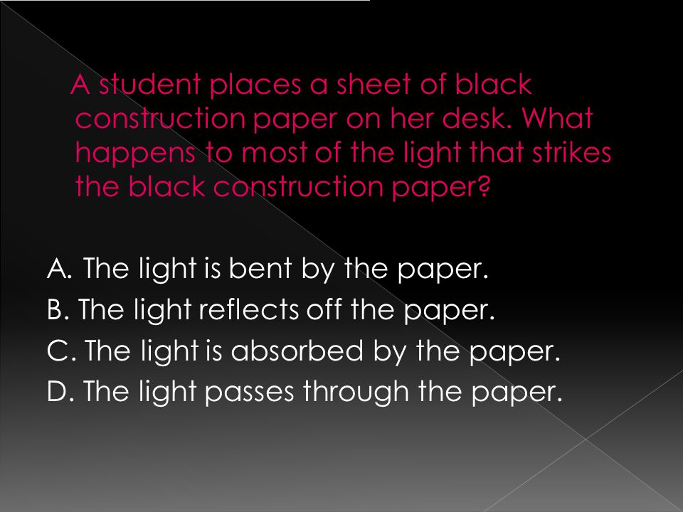 A student places a sheet of black construction paper on her desk