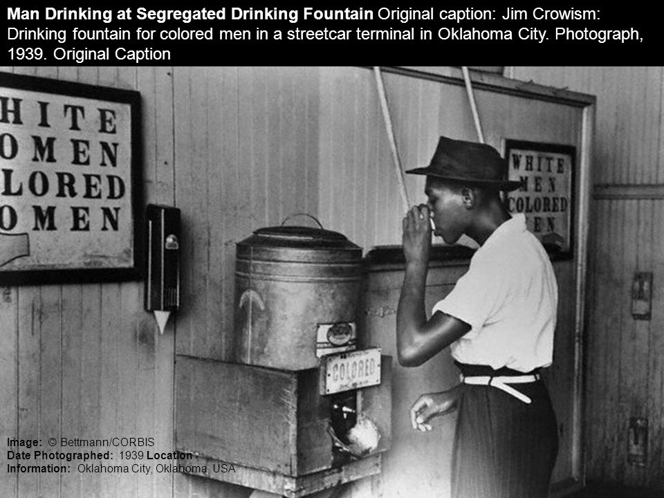 Man Drinking at Segregated Drinking Fountain Original caption: Jim Crowism: Drinking fountain for colored men in a streetcar terminal in Oklahoma City. Photograph, 1939. Original Caption