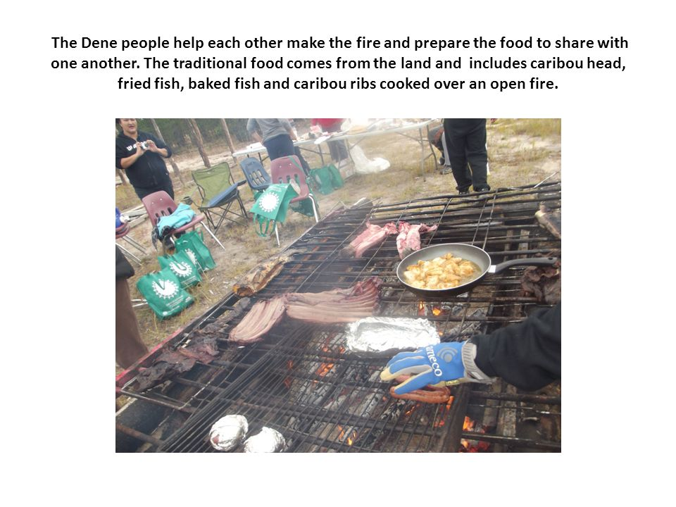 The Dene people help each other make the fire and prepare the food to share with one another.